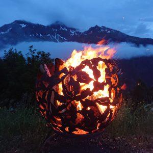 Feuerschale brennendes Holz im Hintergrund wolkenverhangen das Montafoner Hochjoch.